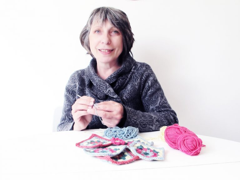 About me - Annie at a white table crocheting