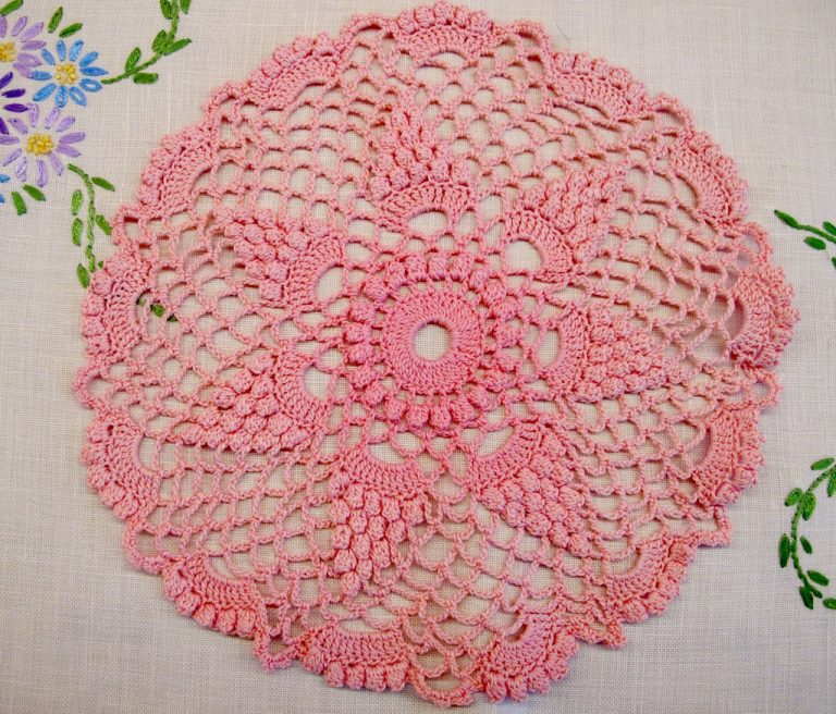 Pink crochet doiley on a linen cloth