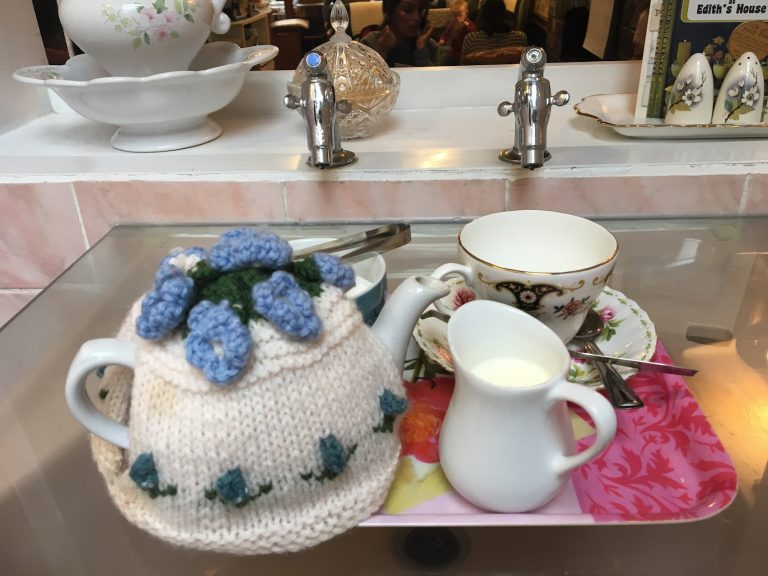 Blue Belle tea cosy on a tray in the bathroom area of Edith's House cafe