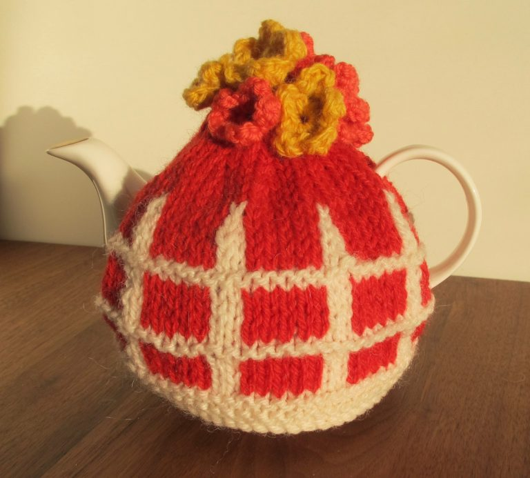 Red tea cosy with white picket fence detail and flowers on top