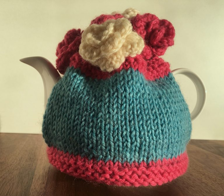 blue tea cosy with pink stripe at bottom and top and pink and white flowers