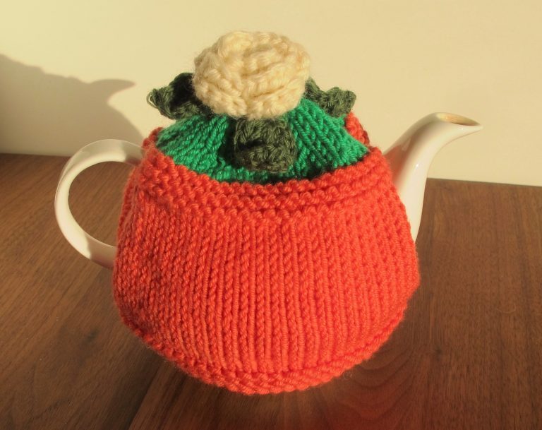 Tea cosy in terracotta colour with white flower and leaves on top
