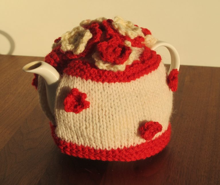 White tea cosy with red stripe at top and bottom and red and white flowers on body and top