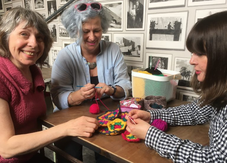 A crochet class with three people at a table
