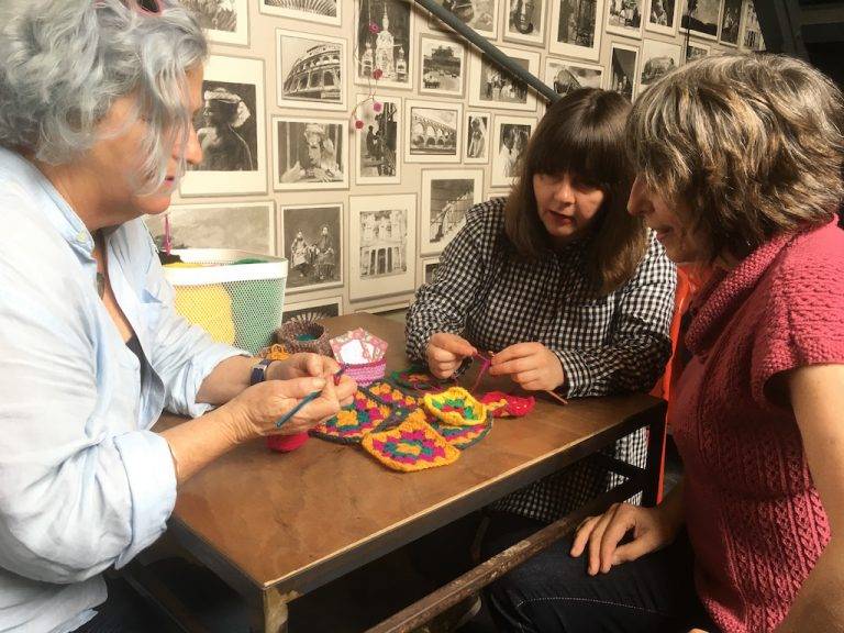 People crocheting at a table