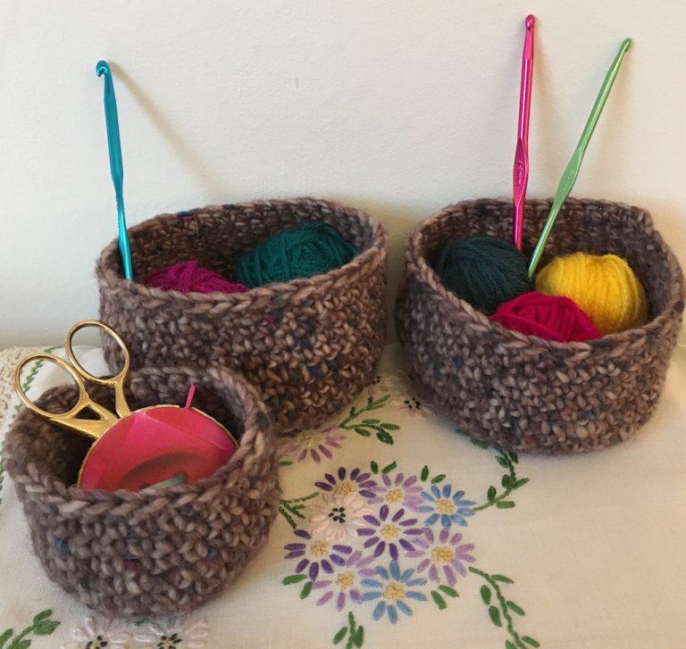 Three tweedy crocheted baskets holding wool and crochet hooks