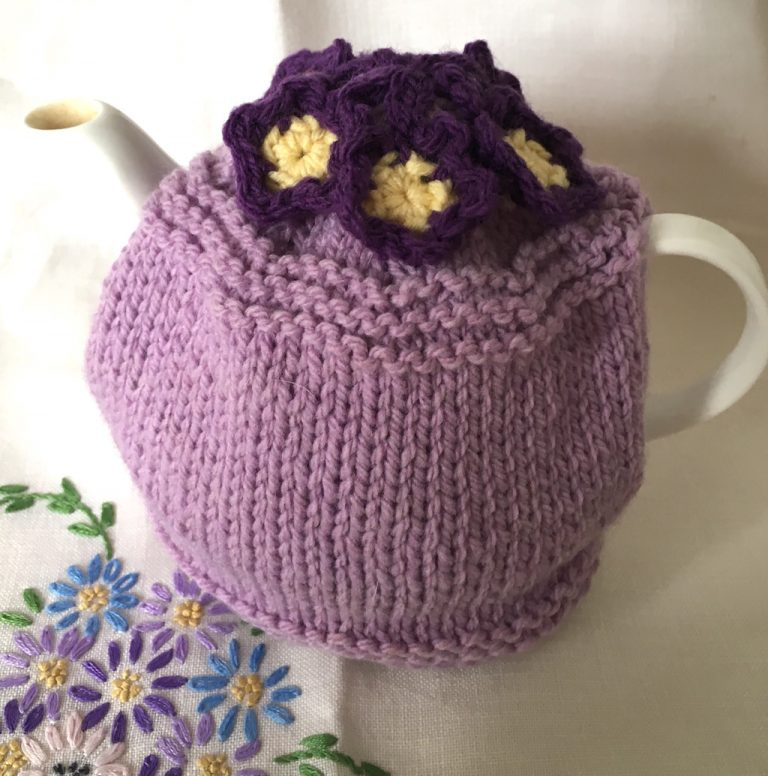 Mauve tea cosy with purple flowers on embroidered cloth