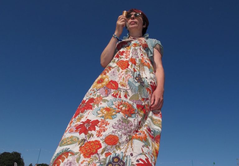 lady in floral maxi dress eating ice cream against blue sky