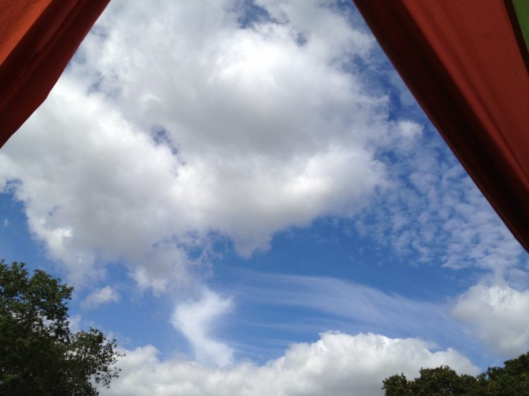 Blue sky with clouds seen from campsite tent