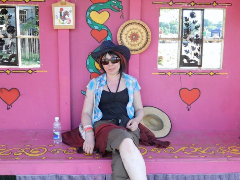 Lady in sunhat sitting in a pink hut at a Glastonbury festival