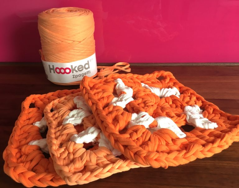 Three oversized granny squares in orange and white