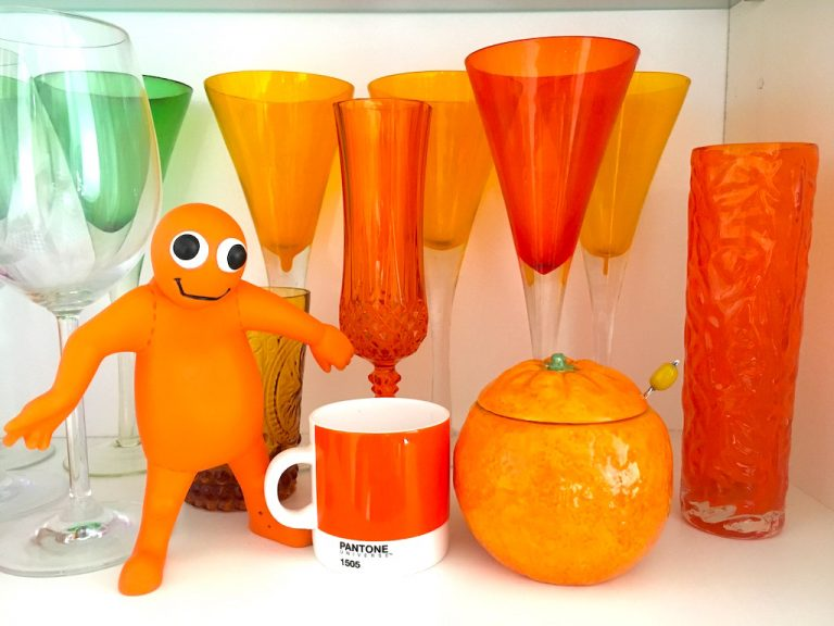 orange glassward and assorted homeware in kitchen cupboard