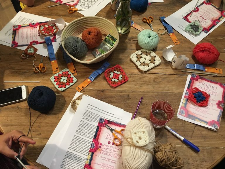 after teaching crochet squares, hooks and leaflets on a wooden table