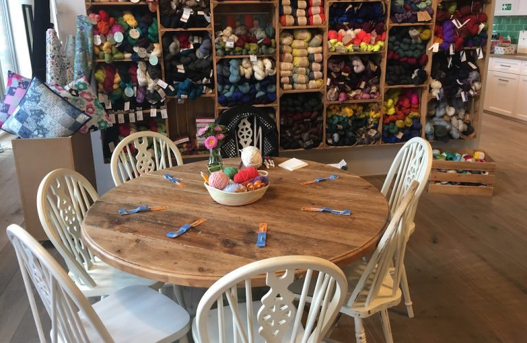 Table set up with crochet hooks, yarn and in front of a display of wool