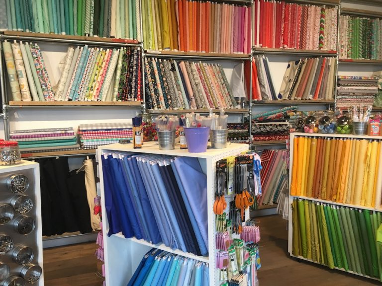 Colourful fabric on shelves at The Village Haberdashery