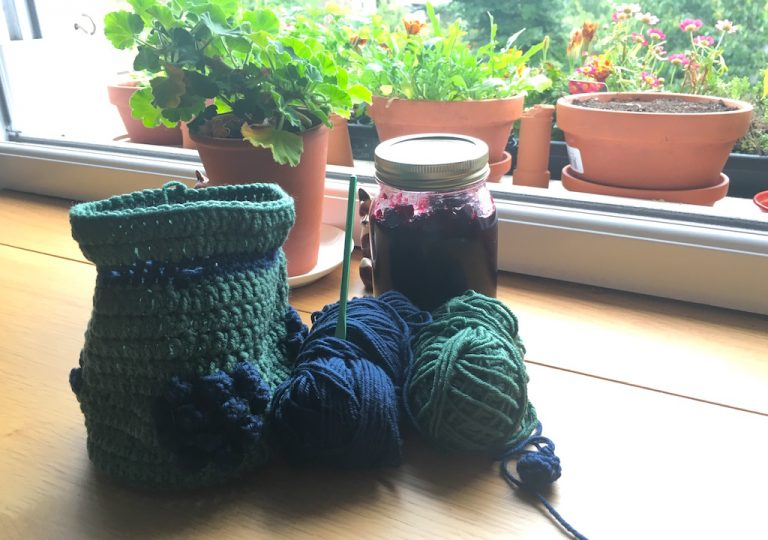 Blackberries bag in progress with jar of jam on table by a plant and window