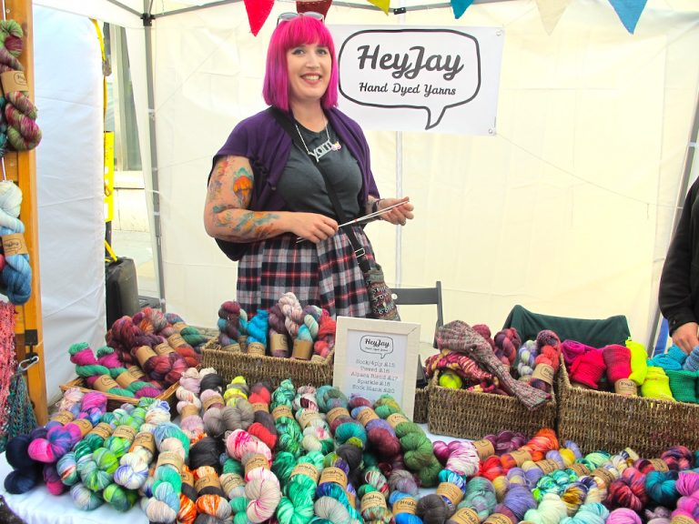 Hanks of colourful HeyJay yarn on a stall with the pink-haired owner behind them