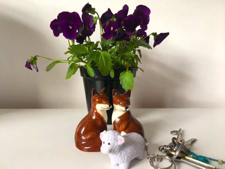 Sheep keyring and fox cruet in front of pot of violets