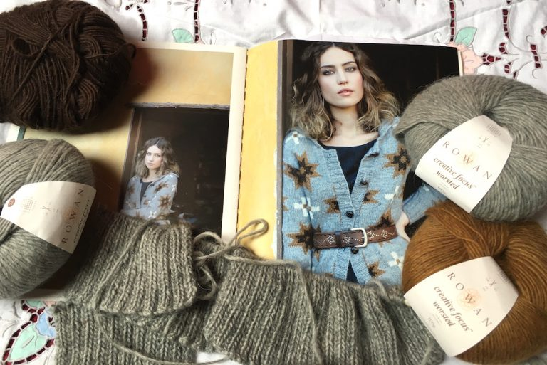 Grey knitting in rib, with balls of yarn and pattern book