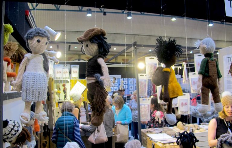 Toft stand at Knitting & Stitching Show with dolls hanging from the top