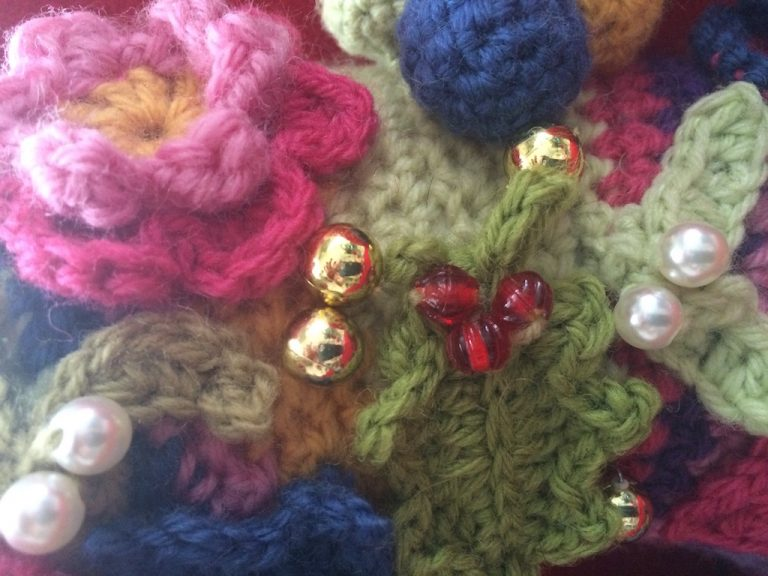 Close up of holly on Christmas crochet wreath