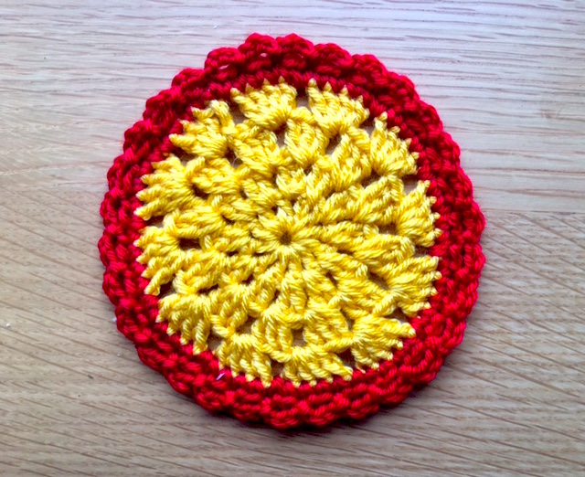 Crochet table mat in yellow and red