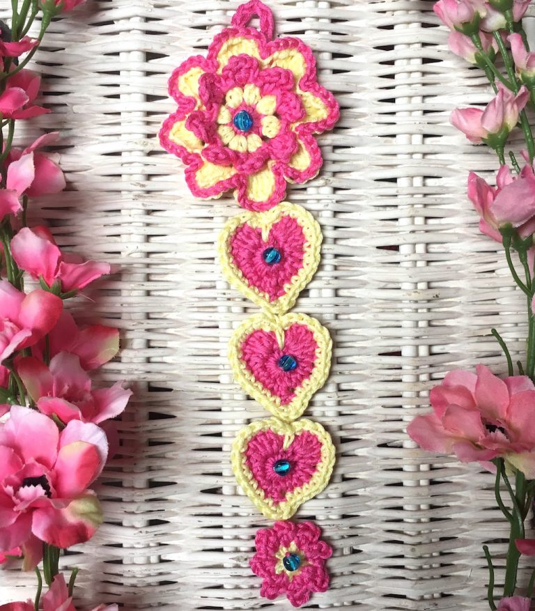 wall hanging made up of crochet hearts and flowers