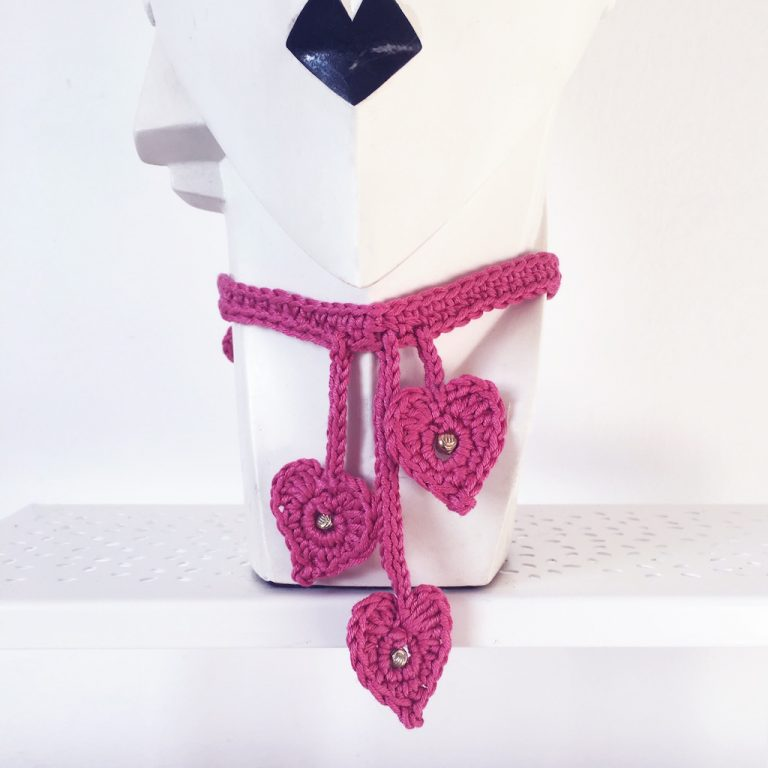pink crochet choker with three hearts on pottery head