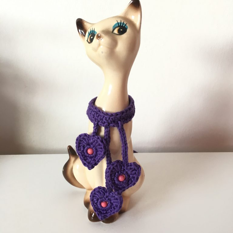 Purple crochet hearts choker on retro pottery cat