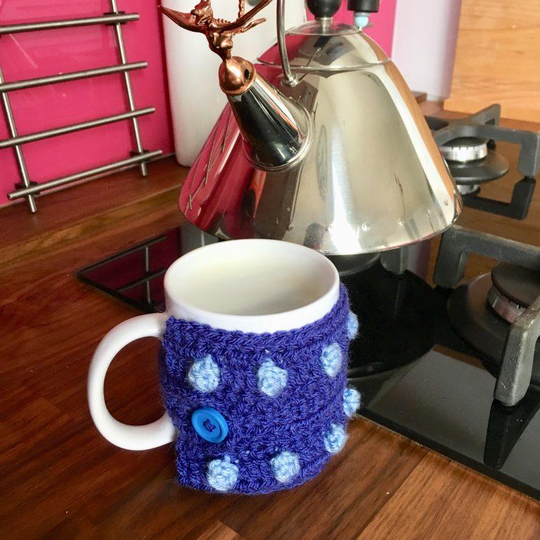 Mug cosy on mug and kettle on hob